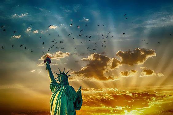 Statue liberté derrière un ciel lumineux